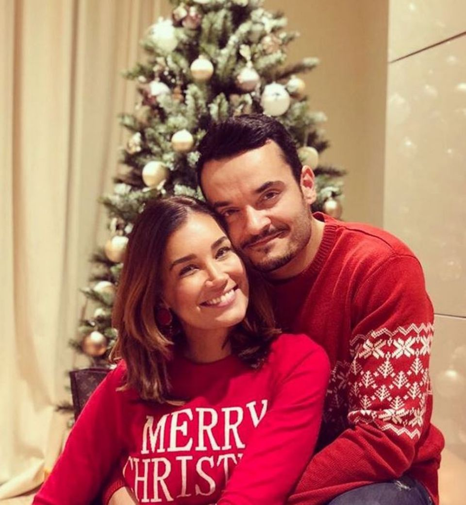 Jana Ina und Giovanni Zarrella präsentieren sich im Partnerlook vor dem Weihnachtsbaum.