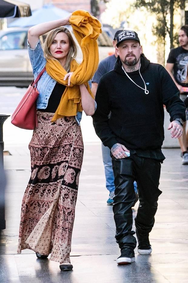 """Es ist wirklich ein seltenes Vernügen, Cameron Diaz und ihren Mann, den """"Good Charlotte""""-Zwilling Benji Madden zusammen beim Date zu sehen. Hier sind die beiden öffentlichkeitsscheuen Stars gerade auf dem Weg ins """"Hamilton""""-Musical in Hollywood. Er trägt wie üblich Schwarz, Cameron hingegen zeigt sich mit gemustertem Rock, Jeans-Jacke und quietschgelbem Schal wesentlich farbenfroher."""