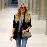 Hinter den Kofferbergen zeigt Sylvie diesen lässigen Reise-Look mit Jeans und Blazer über dem grauen Pullover. Guten Flug und viel Spaß in Miami!