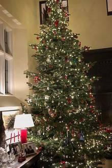 Die hohen Decken machen es möglich: Im Londoner Traumhaus des ehemaligen Supermodels Claudia Schiffer steht ein gigantischer Weihnachtsbaum. Flankiert wird er von dunklen Holzmöbeln, Glasfiguren und Fotos (unter anderem ein Hochzeitsfoto) von Claudia Schiffer und Ehemann Matthew Vaughn.