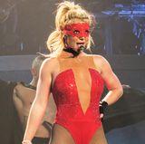 ...oder im hautengen roten Body und Netzstrümpfen. Die Spitzen-Maske setzt dem skurrilen Look das i-Tüpfelchen auf.
