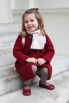 """Charlottes roter """"Razorbil""""-Mantel (ca. 130 Euro) passt farblich perfekt zu ihren """"Mary Jane""""-Schuhen des spanischen Labels """"Dona Carmen"""" (ca. 30 Euro). Mit den Strumpfhosen (ca. 12 Euro) und dem rosafarbenen Schal (ca. 140 Euro, im Set mit einer passenden Mütze) von """"Amaia Kids"""" ist die Prinzessin schön warm eingepackt. Ihre rote Haarschleife und der rosafarbene Mini-Rucksack sind von """"Cath Kidston"""" (ca. 28 Euro)."""