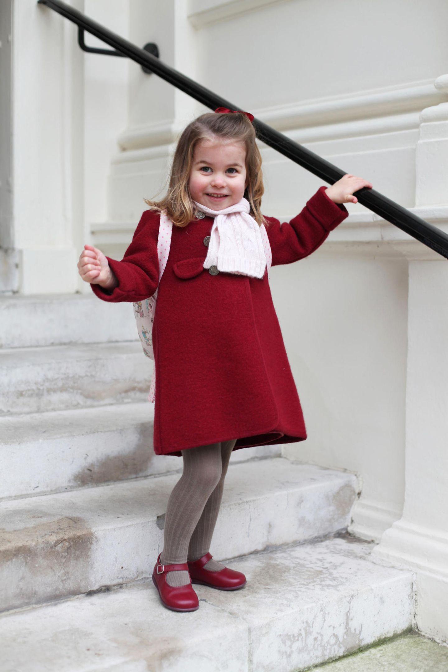 """Die Fotos von Prinzessin Charlottes erstem Tag im Kindergarten (""""Willcocks Nursery School"""") lassen uns dahinschmelzen. Darauf trägt sie einen roten Mantel mit dazu passenden Schühchen. Alles scheint aufeinander abgestimmt zu sein, auch der rosa Schal zum rosa Rucksack passt perfekt. Der gesamte Look hat knapp 340 Euro gekostet."""