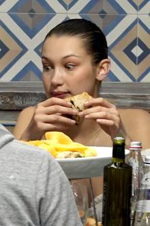 """Die mailändische Pizzeria Assaje freut sich über prominenten Besuch: Keine Geringere als Supermodel Bella Hadid gönnt sich ihre italienischen Leckereien. Bellas schockierter Blick allerdings dürfte Kellnern den Atem stocken lassen, denn er regt die Fantasie zu herrlich gemeinen Interpretationen an. Zum Beispiel: """"Iiihhh, eine Ratte!"""", """"So etwas Furchtbares habe ich noch nie im Mund gehabt!"""" oder """"Warum ist der Tisch so dreckig?"""" Liebe Kellner, wir fühlen mit euch."""