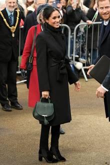 """Erneut hat Meghan Markle mit ihrem Outfit voll ins Schwarze getroffen. Und das im wahrsten Sinne des Wortes. Sie hält ihren Look komplett einfarbig, setzt mit ihrer Handtasche jedoch einen tollen Akzent. Diese stammt von DeMellier, heißt """"Mini Venice"""" und kostet 375 Euro. Ihren Mantel hat übrigens Stella McCartney designt, die """"Kiki""""-Stiefel sind von Tabitha Simmons. Alle Labels kommen aus London. Die Queen ist darüber sicherlich amused."""