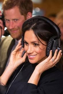 Sogar mit wuchtigen Kopfhörern sieht sie cool aus! Stolz schaut Prinz Harry seine Verlobte Meghan an, als die beiden eine Radiostation in London besuchen