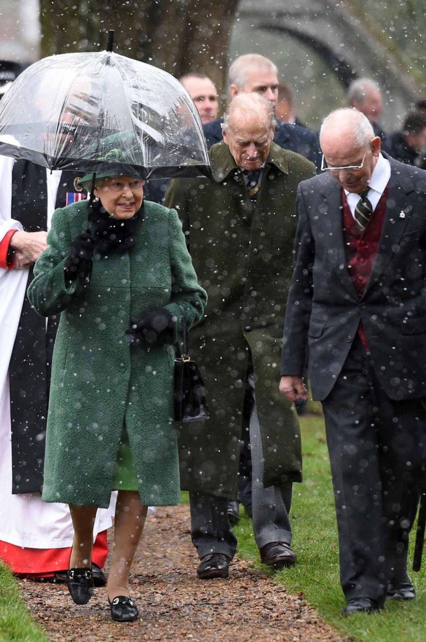 """21. Januar 2018  Die Queen besucht mit Ehemann Philip, Sohn Andrew und den Enkelinnen Eugenie und Beatrice die """"St Lawrence-""""Kirche in Norfolk. Die Geistlichen, die die Queen vor der Kirchentür empfangen, müssen - ebenso wie die übrigen Windsors - waren offenbar nicht so gut auf den Schnee vorbereitet wie die Elizabeth II., die gut gelaunt und beschirmt erscheint."""