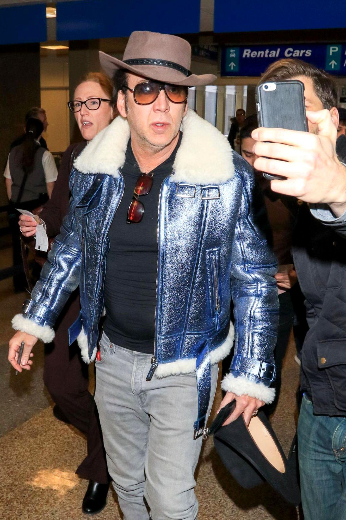 Am Flughafen der Stadt Salt Lake City wird Nicolas Cage beim Autogramm-Schreiben und Selfie-Knipsen gesichtet. Bei näherer Betrachtung fallen zwei Merkwürdigkeiten auf: Erstens, der Schauspieler hat zwei Hüte und Sonnenbrillen dabei, und zweitens er sieht einem Rockmusiker zum Verwechseln ähnlich ...