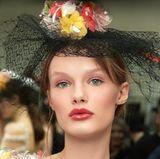 Zusätzlich zu den opulenten Kreationen von Designer Karl Lagerfeld tragen die Models Kopfschmuck mit floralen Akzenten.