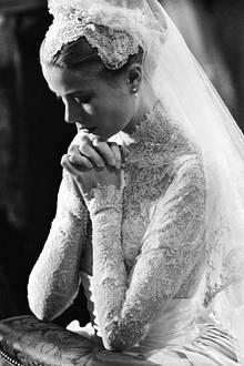 """Wie bereits Königin Victoria entscheidet sich Grace Kelly bei ihrer Hochzeit mit Fürst Rainier gegen ein Diadem. Stattdessen trägt sie einen mit Spitze besetzten Kopfschmuck, auch """"Juliet Cap"""" genannt."""