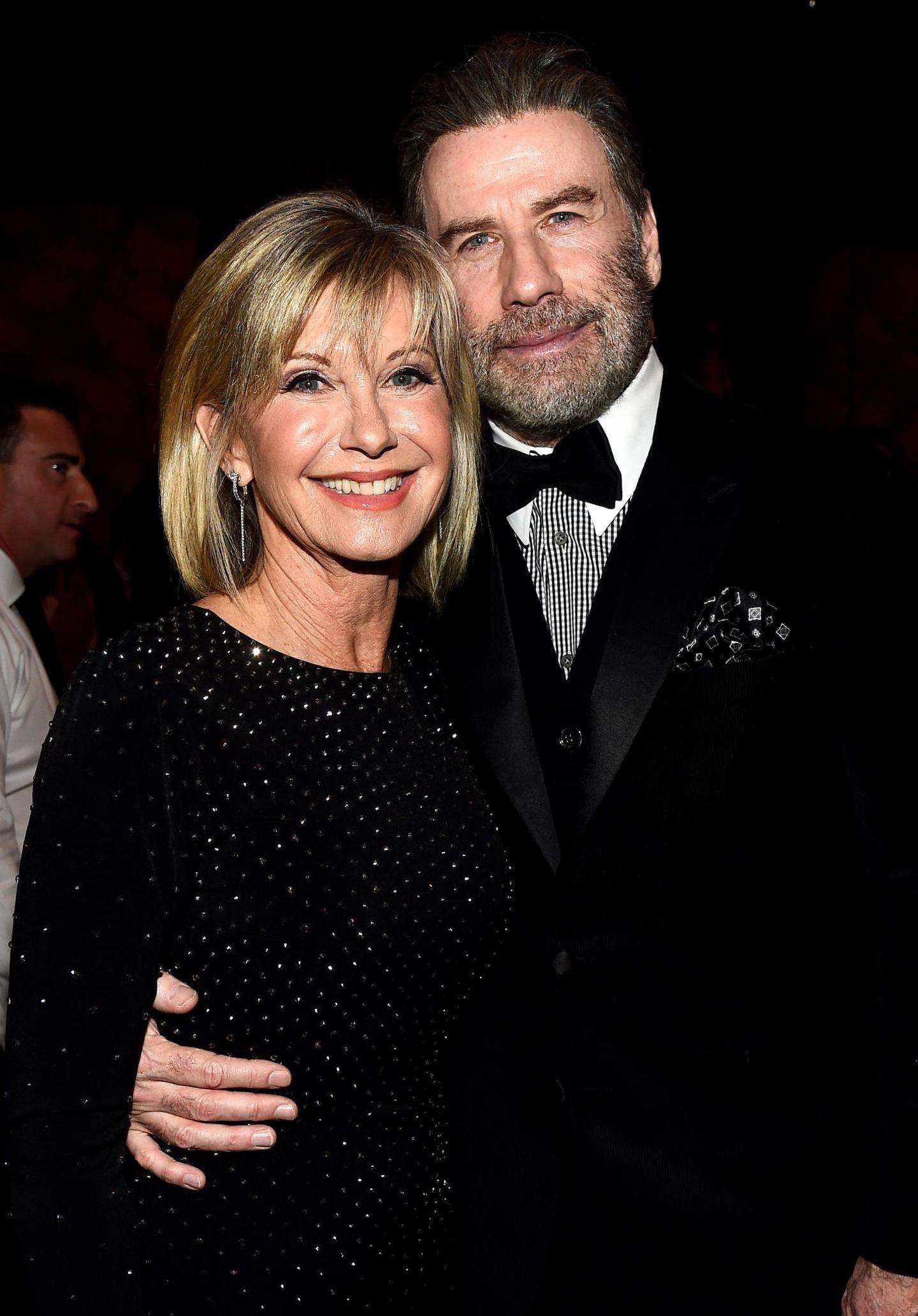 """Während der """"Black Tie""""-Gala in Los Angeles treffen Olivia Newton-John und John Travolta freudestrahlend aufeinander und lassen Fans in tanzfreudigen Erinnerungen schwelgen."""