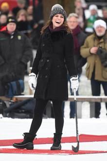 Trotz des kalten Wetters zeigt sich Herzogin Catherine am ersten Tag ihres Schweden-Besuchs in bester Laune: In einem schwarzen, doppelreihigen Burberry-Mantel, unter dem sie - passend wie immer - einen Pullover des schwedischen Labels Fjallraven trägt, und in dicken Winterboots von Sorel versucht sie ihr Glück beim Bandy-Spiel.