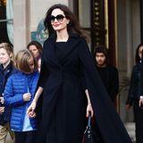 """Mit ihrem eleganten """"Sightseeing""""-Outfit könnte Angelina Jolie direkt auf den Red Carpet gehen. Ihr schwarzer Cape-Mantel ist farblich auf ihre Handtasche und die Pumps abgestimmt."""