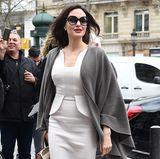 In einem eleganten Kleid verzaubert Angelina Jolie die Champs-Élysées. Besonders schön ist daran die Silhouette: Das abgesetzte Schößchen spiegelt sich in dem leichten Mermaid-Saum wieder und wird wunderbar von Angelinas schwungvollem Cape aufgenommen.