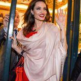 Diesen strahlend schönen Look hat Angelina Jolie ebenso im Gepäck. Über ein enges, rotes Kleid hat sie einen Ponscho gelegt, der mittlerweile ihr Markenzeichen ist. Das Highlight-Piece: definitiv ihre knallrote Handtasche von Louis Vuitton.