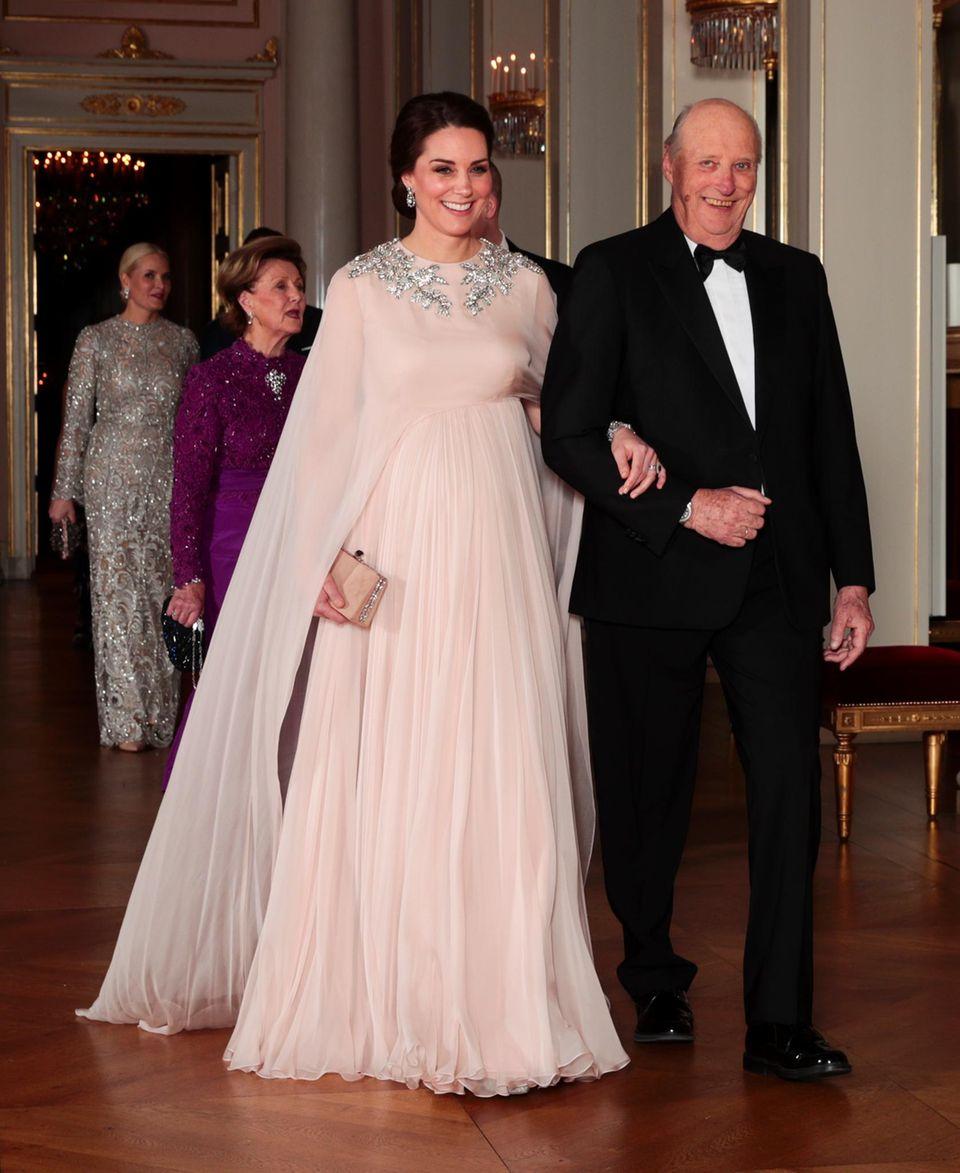 Norwegen - Tag 2  Die schwangere Herzogin Catherine wird von König Harald zum Tisch des offiziellen Dinners am Abend begleitet. Catherine in einem pinkfarbenen Abendkleid von Alexander McQueen, das über ihren wachsenden Babybauch gleitet. Dazu trägt sie Diamantohrringe und das dazu passende Armband. Beides erhielt sie von Prinz Philip als Hochzeitsgeschenk.