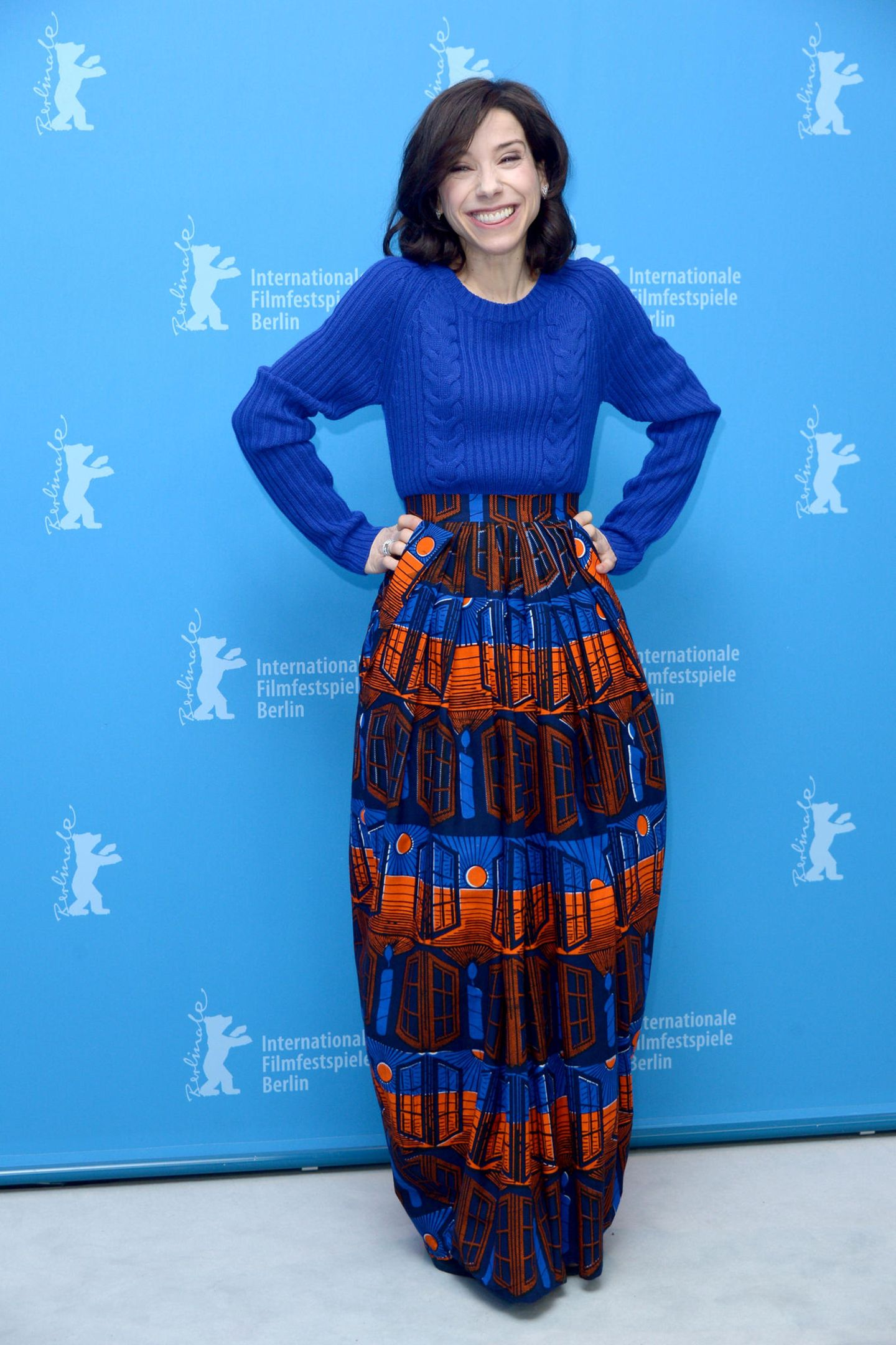 """Ungewöhnlich und großartig: Sally Hawkins leuchtet bei der Pressekonferenz für """"Maudie"""" in dieser royalblauen, orangefarbenen Strickpullover-Rock-Kombi."""