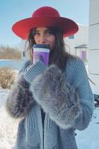 Um gegen die Kälte anzukämpfen, hat sich Taylor Hill dick eingepackt und wärmt sich mit einem Heißgetränk.