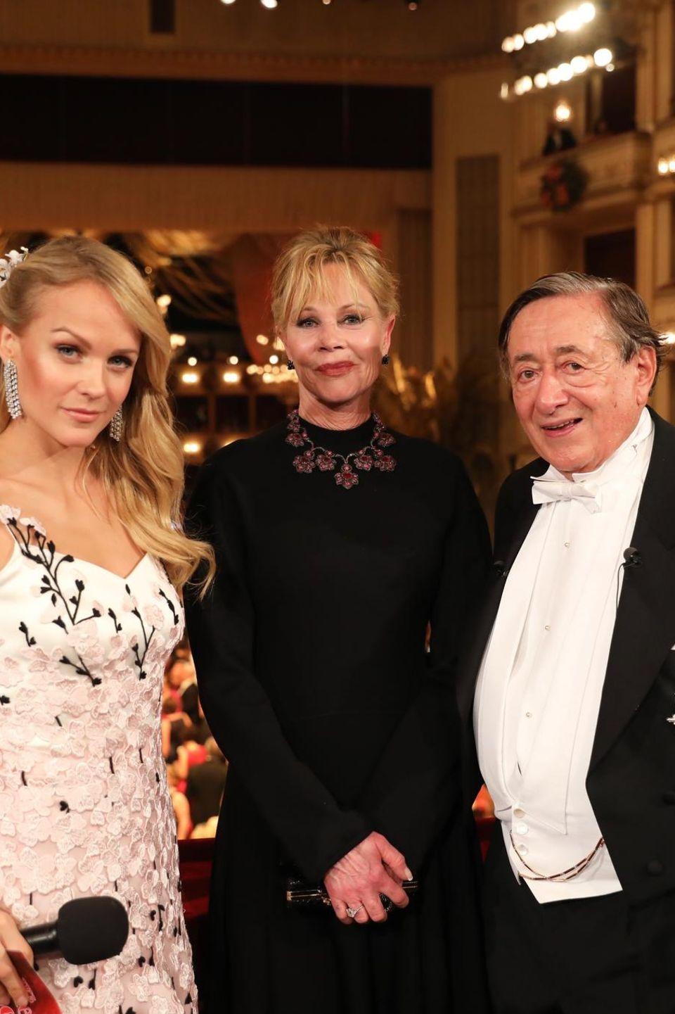 Moderatorin Mirjam Weichselbaum posiert im floral bestickten Abendkleid den beiden wichtigsten Personen des Wiener Opernballs: Gastgeber Richard Lugner und sein diesjähriger Stargast Melanie Griffith.