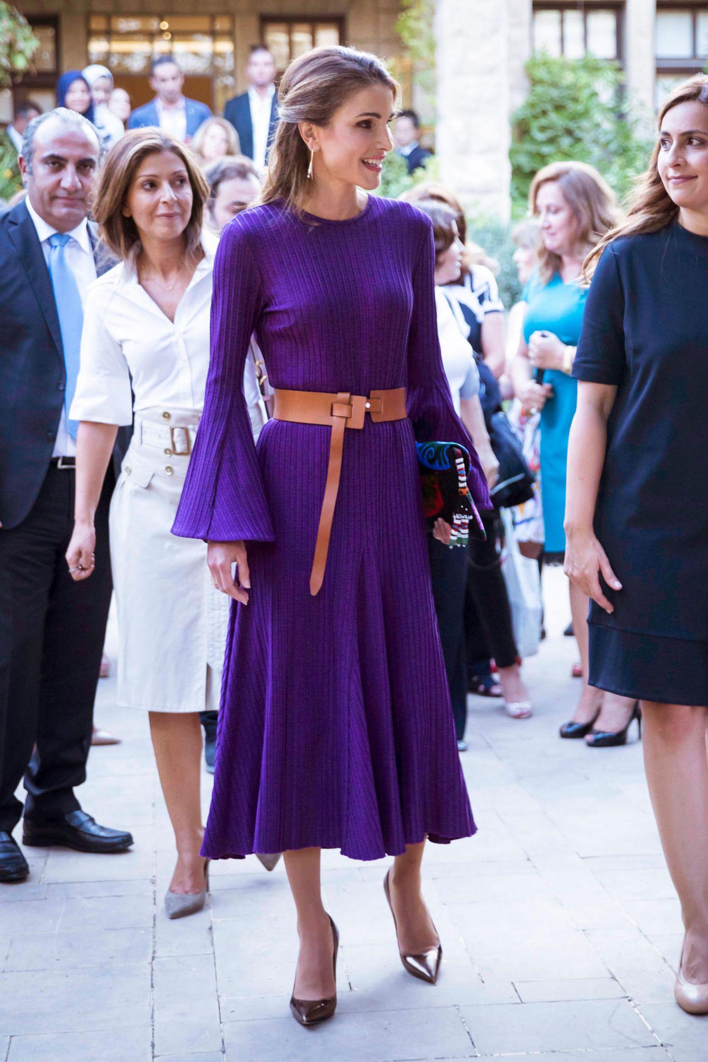 Bei einer Handwerksmesse überstrahlt Königin Rania im lilafarbenen Kleid mit Glockenärmeln alle anderen Besucher.