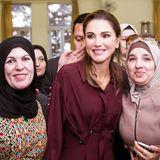 Im eleganten, weinroten Seidendress passt sich Königin Rania farblich toll ihren royalen Fans in einem Gemeinschaftszentrum in Amman an.