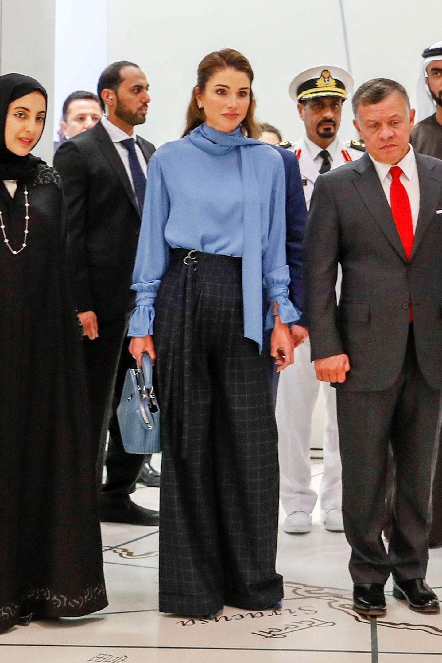 """Luxus-Queen im Louvre: In taubenblauer Seidenbluse, stylischer, karierter Marlene-Hose des aufstrebenden Designer-Labels Reemami aus den Vereinigten Arabischen Emiraten und mit der nicht ganz günstigen, hellblauen """"Dotcom""""-Bag von Fendi (ca. 1.850 Euro) bezaubert Königin Rania an der Seite von König Abdullah bei ihrem Besuch im neuen Louvre Abu Dhabi."""