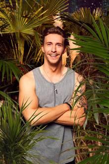 Vor seinem Einzug ins Dschungelcamp zeigt sich David Friedrich kräftig und lachend in siegessicherer Pose. Der Musiker brachte sich während seiner vorhergehenden Tour so richtig in Form und zeigte sich auf Instagram immer wieder beim Trainieren im Gym.