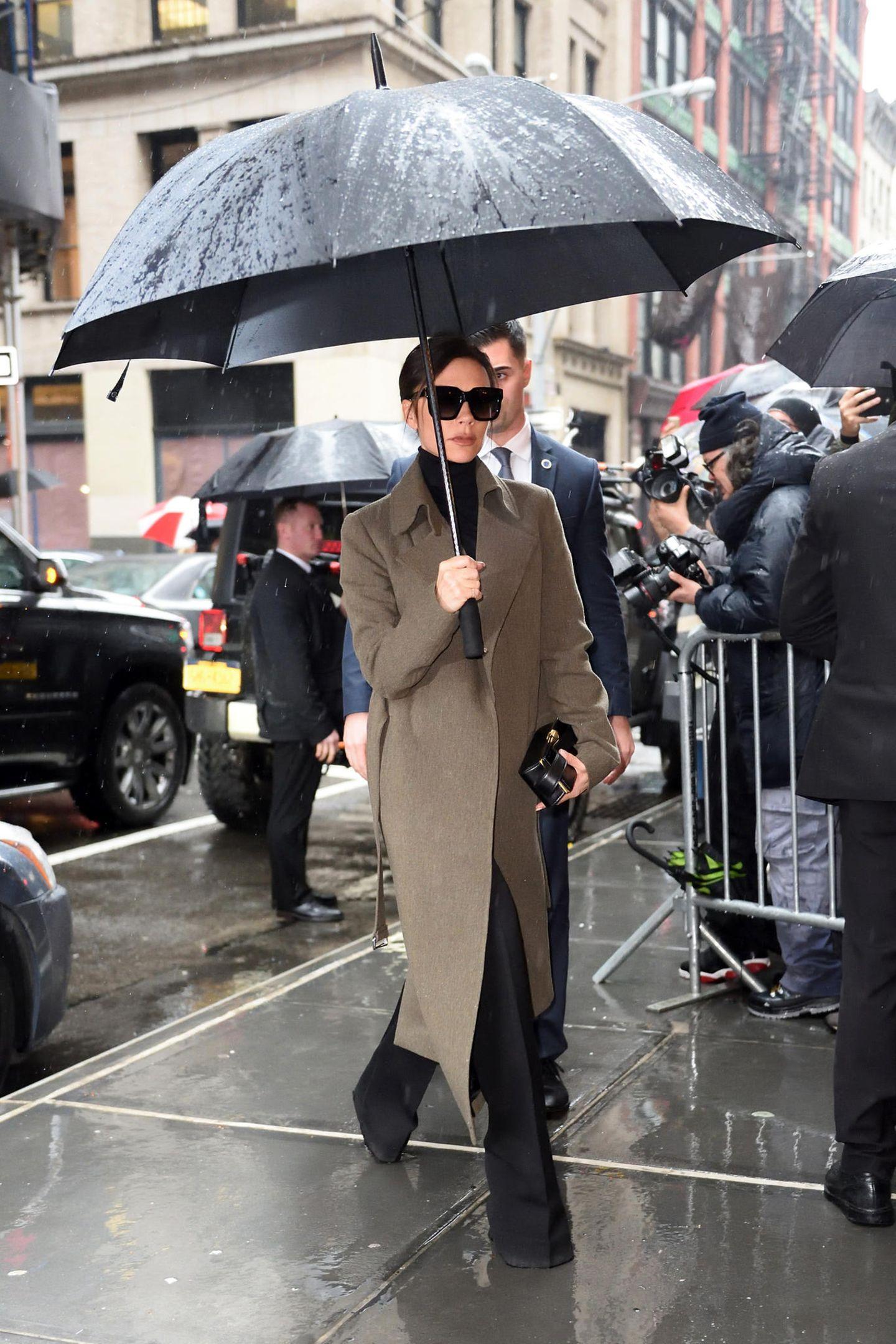 Auf dem Weg zu ihrer eigenen Fashion-Show schützt sich Victoria mit Schirm und elegantem, grau-khakifarbenem Mantel vor dem New Yorker Mistwetter.
