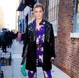 Ihr lässige Lederjacke kombiniert Topmodel Nina Adgal mit einem lilablau leuchtende, floralen Seiden-Jumpsuit.
