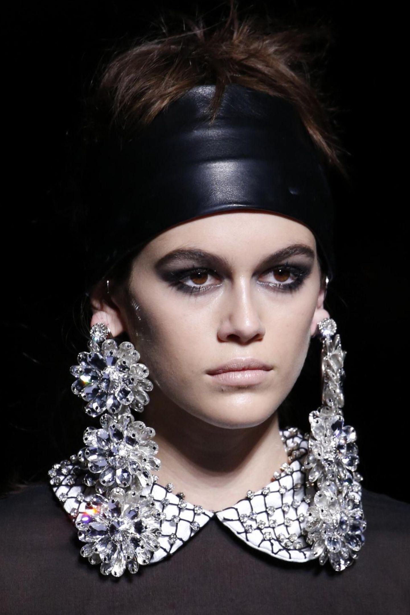 Kaia Gerber ist momentan von keiner Fashion Week wegzudenken: Auf dem Laufsteg von Tom Ford in New York werden ihre dunklen Rehaugen durch Smokey Eyes und einen dunklen Lidstrich betont. Der Rest des Make-up ist eher farblos und schlicht.