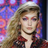 Auch Schwester Gigi Hadid läuft für die amerikanische Designerin über den Laufsteg. Zu ihrem blassen Teint sieht das Augen-Make-up in verschiedenen Rot- und Lilatönen noch dramatischer aus. Auch sie trägt ihre blonde Mähne auf eine Seite gekämmt und XXL-Ohrringe.