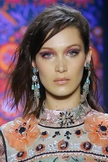 """Auf dem Runway der """"Anna Sui""""-Show in New York wird es farbenfroh und verspielt. Topmodel Bella Hadid trägt mehrfarbigen Lidschatten, auffällige Ohrringe und wildes Haar."""