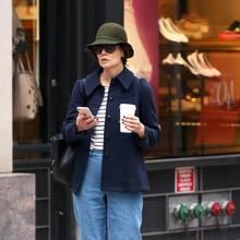 Im kastig geschnittenen Boyfriend-Look, samt olivgrünem Schlapphut und Coffee-to-go, genießt Katie ganz entspannt ihre Shopping-Tour.