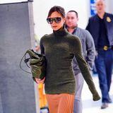Am JFK-Airport in New York flaniert Victoria in einem olivfarbenen Rollkragenpullover und orangefarbenem Plissee-Rock zu ihrem Gate.