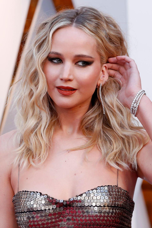 Wilde Lockenpracht, Katzenaugen und rote Lippen: Jennifer Lawrence geht mit ihrem Oscar-Look aufs Ganze.