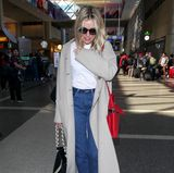 Denn auch Sienna wurde am Flughafen erwischt und lässt es auf ihrer Rückreise Outfit-technisch ein wenig entspannter angehen: Zu Jeans und T-Shirt kombiniert sie einen langen, kuscheligen Cardigan.
