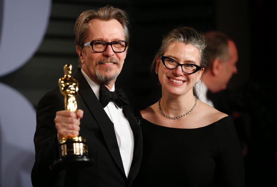 """Yes! Da ist das Ding! Wenn einer was zu feiern hat, dann er. Gary Oldman präsentiert neben EhefrauGisele Schmidt seinen Goldjungen. Der Schauspieler gewann den Oscar in der Kategorie """"Bester Hauptdarsteller""""."""
