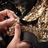 Es folgt das Paillettenkleid von Sandra Bullock. Hier zu sehen: Näharbeiten am Kragen mit Fingerhut und Nadel.