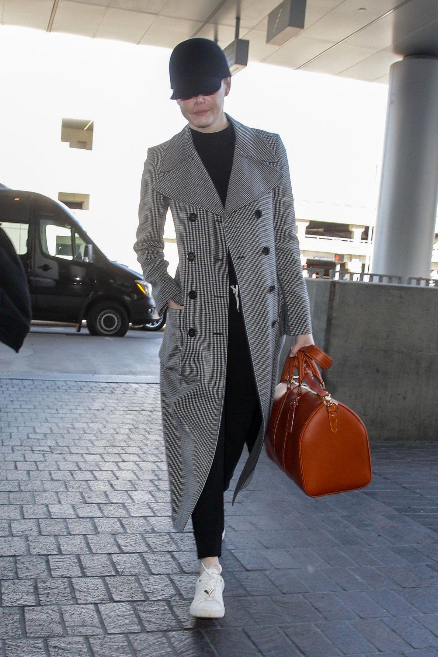 Emma Stone müsste sich für ihr Airport-Outfit eigentlich nicht verstecken. Den Sherlock-Look ihres Mantels bricht sie durch coole Sneaker und eine legere Hose. Das Highlight bleibt allerdings die cognacfarbene Tasche.