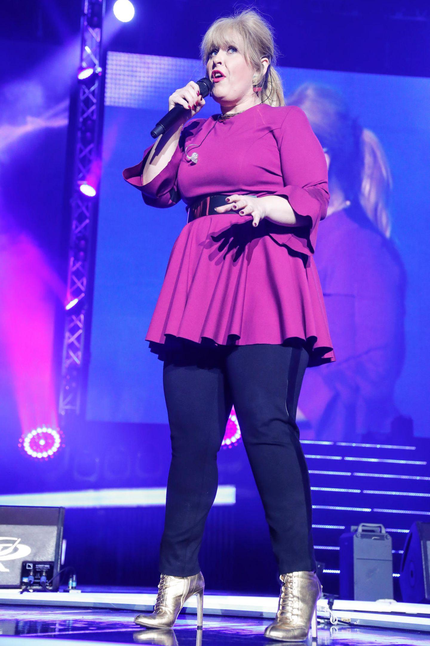 """Bei der """"Schlagernacht des Jahres"""" in Hamburg glänzte Maite Kelly in einem kurzen A-Linien-Kleid und blickdichter Leggings auf der Bühne. Ein Gürtel und der Schnitt des Kleides betonen ganz deutlich, dass die Sängerin erneut einige Kilos abgespeckt hat."""