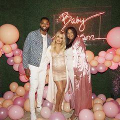 Die hochschwangereKhloé Kardashian posiert mit ihrem Freund und Bald-Papa Tristan Thomson und dessen Mutter Andrea Thompson.Khloé trägt ein hellrosa Kleid mit Glitzerapplikationen, dass sich um ihren Babybauch schmiegt und kombiniert dazu einen passenden cremefarbenen Mantel.