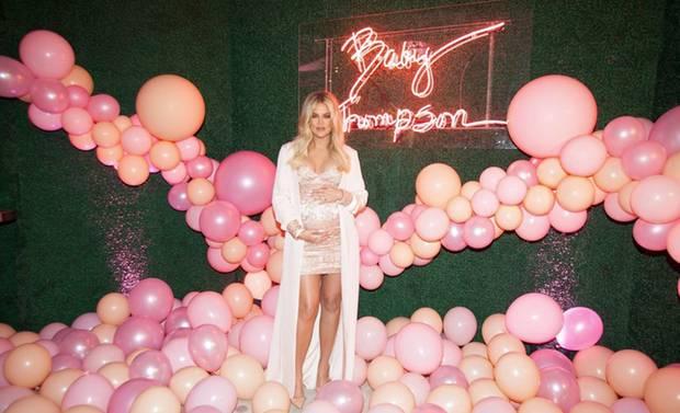 """Die überglücklicheKhloé Kardashian präsentiert sich strahlend schön umzingelt von etlichen, pinken Luftballons und einer Neon-Leuchtschrift mit den Worten """"Baby Thompson""""."""