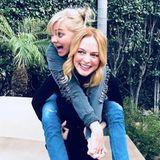 Heather Graham trägt ihre Freundin Anna Faris huckepack. Die beiden Freundinnen sind gerade dabei einen gemeinsamen Podcast aufzunehmen.