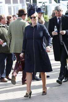 Bestens gelaunt besucht die pferdebegeisterte Zara Philips auch am vierten Tag das Cheltenham Festival, und trägt bei sonnigem Wetter dieses elegante Kostüm in Dunkelblauüber ihrem Babybauch.
