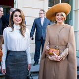 Königin Máxima trägt unter dem Mantel ein langärmeliges Spitzenkleid von Claes Iversen, das nur dank der offenen Ärmel rausblitzt. Königin Rania hingegen hat ihren Mantel abgelegt und zeigt, dass sie darunter einen dunkelgrauen Bleistiftrock und eine weiße durchsichtige Bluse trägt.