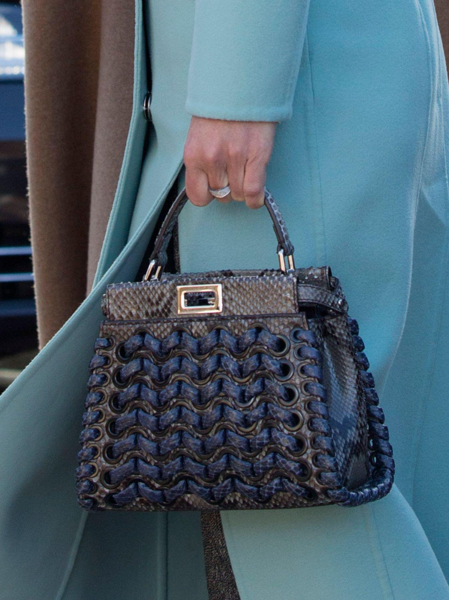 """Der Hingucker ihres Outfits ist jedoch die """"Peekaboo""""-Tasche von Fendi. In blau-schwarzem Python-Leder und mit Webeelementen ist sie ein echtes Wow-Accessoire."""