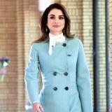Tagsüber trägt Königin Rania einen hellblauen Mantel aus der Herbst/Winter-Kollektion 2017 von Salvatore Ferragamo. An der Taille wird er durch doppelreihige Knöpfe zusammengehalten, unten hat er hohe Schlitze. Dazu trägt sie ein helles Halstuch und hellblaue Pumps.
