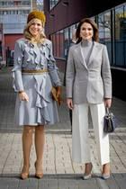 """Im Gegensatz zu Königin Máxima entscheidet sich Königin Rania für eine Blazer-Hosen-Kombination: Sie trägt eine weiße Culotte mit Bügelfalte und einen grauen Blazer von Salvatore Ferragamo. Dazu kombiniert sie ihre """"Peekaboo""""-Tasche von Fendi und Ohrringe von Nikos Koulis und Pumps von Gianvito Rossi."""