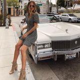 In einem gestreiften Kleidchen und hellbraunen Stiefeletten und runder Sonnenbrille zeigt Ann-Kathrin uns den perfekten California-Look. Lässig posiert sie auf einem Oldtimer.