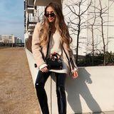In einer coolen Latexhose und mit hellem Strickpulli läutet Ann-Kathrin Brömmel den Frühling ein. Dazu kombiniert sie schwarze Wildlederstiefeletten von Louis Vuitton und eine Strickjacke von Dior. Mit einer XXL-Sonnenbrille bekommt der Look den extra glamourösen Touch.